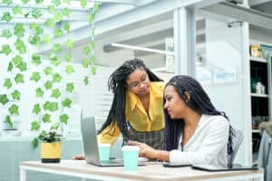 Two data analysts learning technical and business skills to advance careers